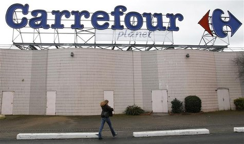 A woman walks below the logo of Carrefour Planet supermarket in Bordeaux