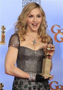"Singer Madonna poses with her award for best original song for ""Masterpiece"" from the movie ""W.E.,"" backstage in Beverly Hills"