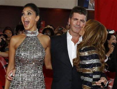 "Paula Abdul kisses the cheek of Simon Cowell as Nicole Scherzinger reacts at the world premiere of ""The X Factor"" in Hollywood"