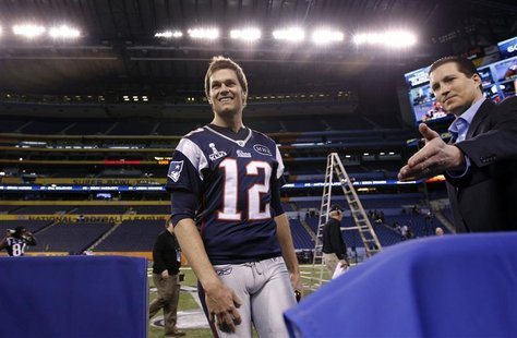 Patriots' Brady is escorted to his interview booth as he arrives at media day for the NFL Super Bowl XLVI in Indianapolis