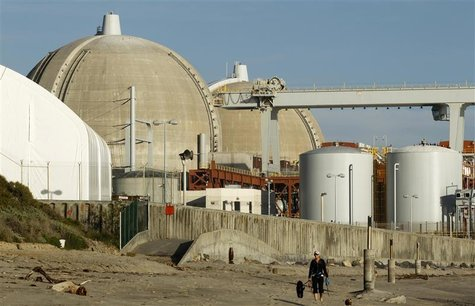 A woman and her dogs walk past the San Onofre Nuclear Generating Station that sits on the shore of the Pacific Ocean in North San Diego Coun