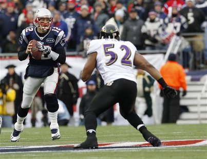 New England Patriots quarterback Brady looks to pass under pressure from Baltimore Ravens Lewis during first quarter of the NFL AFC Champion
