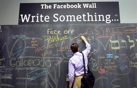 An employee writes a note on the message board at the new headquarters of Facebook in Menlo Park