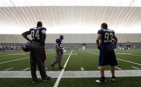 Giants players Kiwanuka, Martin, and Blackburn wait on the sidelines during practice for the NFL Super Bowl XLVI in Indianapolis