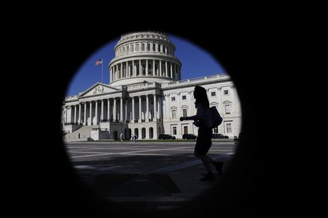 A woman walks past the U.S. Capitol dome, seen through a porthole in nearby brick-work, in Washington