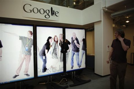Software Engineer Arthur views a scrolling employee photo collage at the Google campus near Venice Beach, in Los Angeles