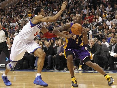 Los Angeles Lakers guard Bryant battles with the Philadelphia 76ers forward Iguodala during second quarter of their NBA basketball game in P