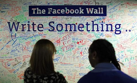 People look at the Facebook wall at their office in New York