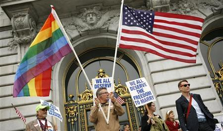 Billy Bradford waves flags outside City Hall after a judge lifted the Proposition 8 stay on same sex marriages at City Hall in San Francisco, California August 12, 2010. Credit: Reuters/Robert Galbraith