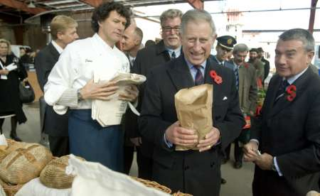 An aide (R) digs money out of his pocket for Britain's Prince Charles (C) to purchase a five dollar loaf of artisans bread, at traditional farmer's market, at the Evergreen Brick Works Restoration site, in Toronto November 6, 2009. Prince Charles and wife Camilla the Duchess of Cornwall are currently on an 11 day tour of Canada. REUTERS/Fred Thornhill (CANADA POLITICS ROYALS)