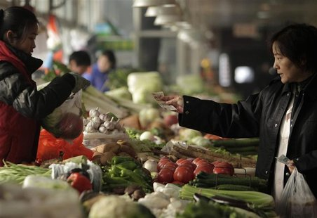 A customer pays for her vegetables at a market in Beijing