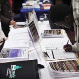 """A man writes down his details at a booth during the """"JobEXPO"""" job fair in New York"""