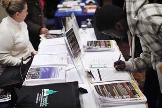 "A man writes down his details at a booth during the ""JobEXPO"" job fair in New York"