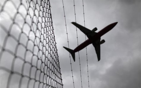 Passenger plane flies over a barbed wire fence