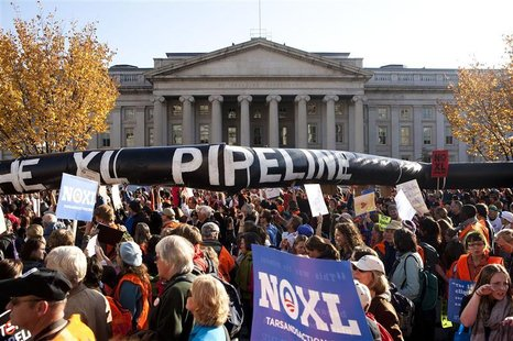 Demonstrators carry a giant mock pipeline while calling for the cancellation of the Keystone XL pipeline during a rally in Washington