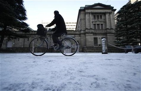Man cycles in front of BOJ headquarters covered with snow in Tokyo