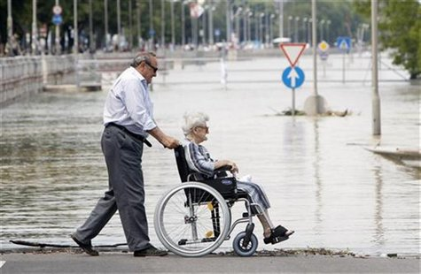 A man pushes his wheelchair-bound mother along the river bank of the flooded Danube river in Budapest