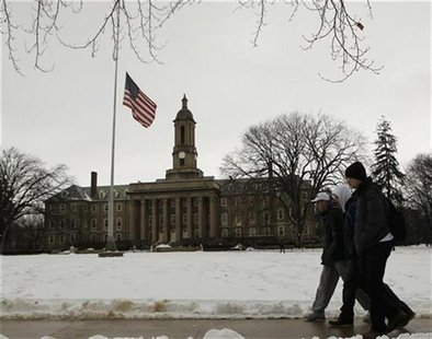 Students pass by a U.S. flag at half-staff at Penn State University in State College Pennsylvania in honor of Joe Paterno