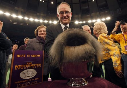 Handler David Fitzpatrick places Malachy a Pekingese into the silver bowl after he won Best In Show at the Westminster Kennel Club Dog Show