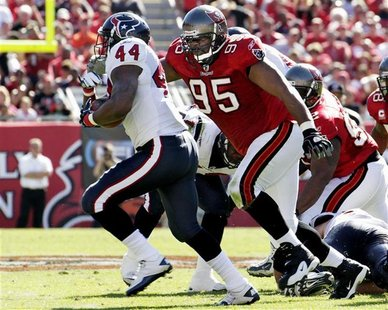 Tampa Bay Buccaneers defensive lineman Albert Haynesworth chases Houston Texans running back Ben Tate during their NFL football game in Tamp