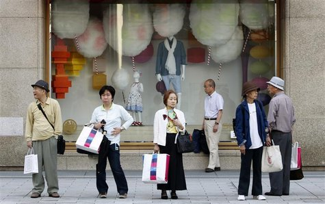 People wait for a bus to arrive in front of a shop window at a department store in Tokyo