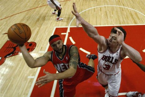 New Jersey Nets' Deron Williams goes to the basket against Chicago Bulls' Omer Asik during the first half of their NBA basketball game in Ch