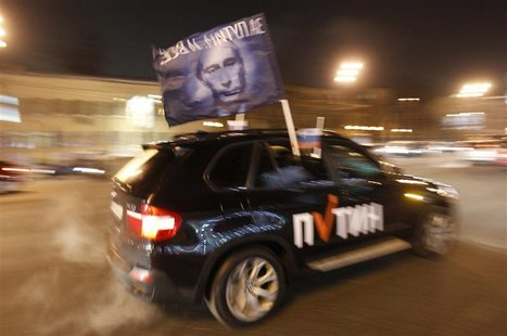 A car drives with a flag showing a portrait of Russian Prime Minister Vladimir Putin during a car rally to show support for Putin's presiden
