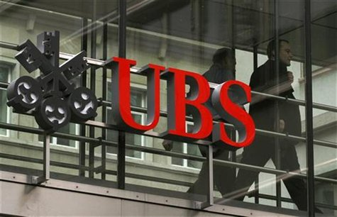 People walk behind the logo of Swiss bank UBS in Zurich