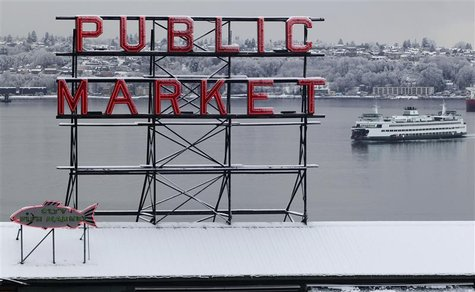 Snow blankets the roof of the famous Pike Place Market as a ferry floats past in Seattle