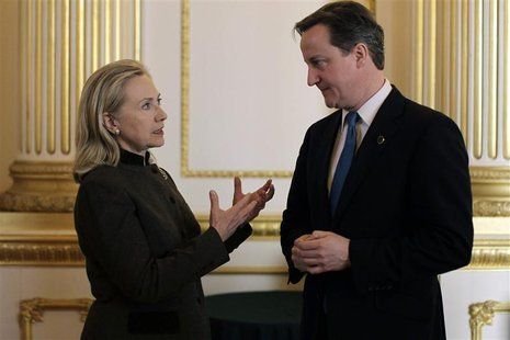 Britain's Prime Minister David Cameron speaks with US Secretary of State Hillary Clinton during the Somalia Conference at Lancaster House in