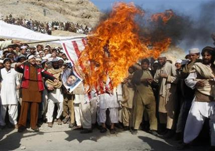 Afghan protesters burn a U.S. flag during a protest in Jalalabad province February 24, 2012. REUTERS/Parwiz