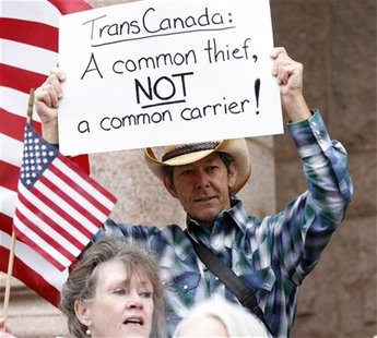 Man holds sign at rally as landowner Crawford is set to battle TransCanada over trenching of her property for the Keystone pipeline in Paris