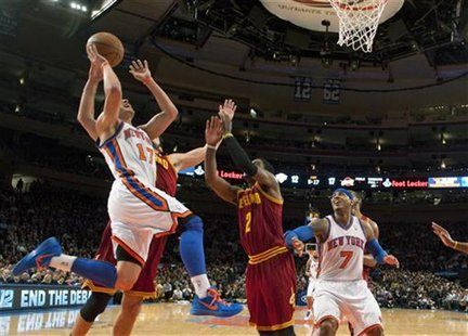 New York Knicks Jeremy Lin loses ball shooting against Cleveland Cavaliers Omri Casspi and Kyrie Irving in NBA game in New York