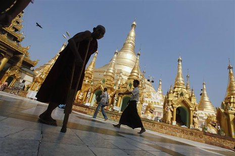 A disabled Buddhist monk walks on the grounds of Shwedagon Pagoda during the 2,600th anniversary of the pagoda in Yangon