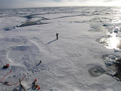 A member of a team of Cambridge scientists trying to find out why Arctic sea ice is melting so fast, walks on some drift ice 500 miles from