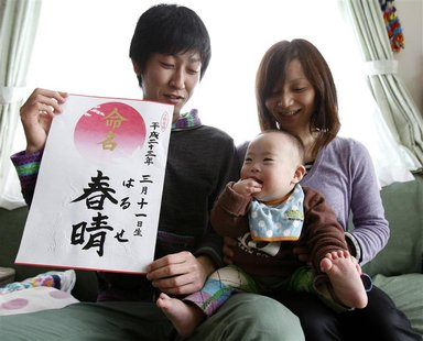 Hiromi Sato holds her son next to her husband during a photo opportunity at their home in Minamisanriku