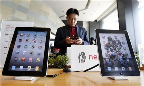 Customer holds Apple Inc iPhone 4 smartphone on display behind company's iPad tablets at headquarters of South Korean mobile carrier KT in S