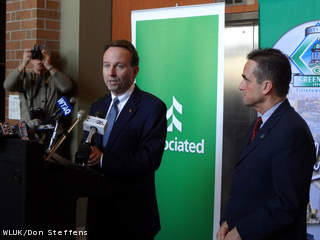 Associated Banc-Corp President/CEO Phil Flynn (left) discusses the company's plan to move its headquarters from Ashwaubenon to downtown Green Bay, March 26, 2012. Green Bay Mayor Jim Schmitt looks on. (courtesy of FOX 11).