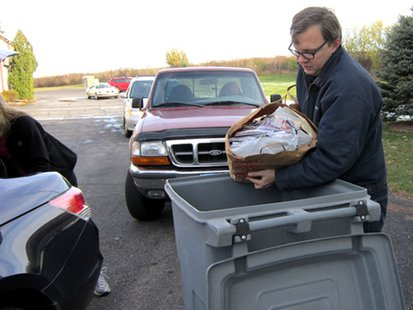 An employee of Access Information Management dumps paper into the shredding bins. (courtesy of Wisconsin Department of Agriculture, Trade and Consumer Protection).