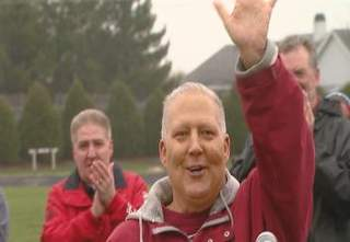 Dan Baker waves to the crowd during the ceremony naming the De Pere high school track after him. (courtesy of FOX 11).