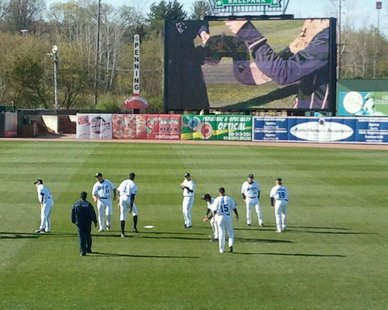 BASEBALL'S BACK: Members of the West Michigan Whitecaps warm up before the new center field scoreboard at Fifth Third Ballpark prior to the home opener against visiting Bowling Green on April 9, 2012.