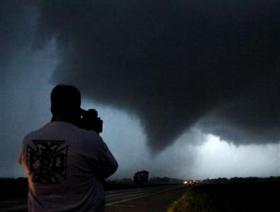 Storm chaser photographer Brad Mack shoots a tornado as it makes its way over the 135 freeway near Moundridge, Kansas, during the third day of severe weather and multiple tornado sightings, April 14, 2012. REUTERS/Gene Blevins