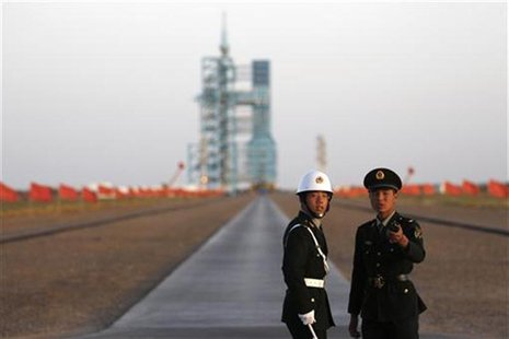 Soldiers stand in front of the Long March II-F rocket loaded with China's unmanned space module Tiangong-1 before its planned launch from th