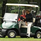 President Barack Obama takes the wheel of a golf cart as he rides with former President Bill Clinton as they play golf at Andrews Air Force
