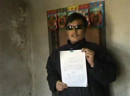 Blind legal activist Chen Guangcheng holds a petition in his village home in Linyi in eastern Shandong province, in this still image taken f
