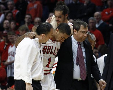 Chicago Bulls' Derrick Rose (C) is helped off the court after getting hurt during the second half of their NBA Eastern Conference quarter-fi