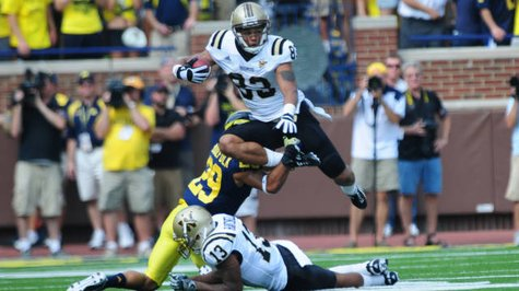 Jordan White(83) hurdles a Michigan defender.