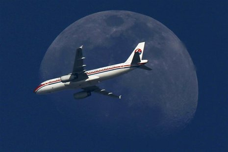 A China Eastern Airlines passenger jet passes in front of the moon over Shanghai in this May 13, 2011 file photograph. REUTERS/Aly Song/File