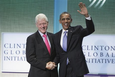 U.S. President Barack Obama (R) greets former U.S. President Bill Clinton after speaking during the Clinton Global Initiative in New York, S