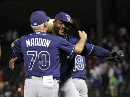 Tampa Bay Rays pitcher Fernando Rodney (R) is congratulated by manager Joe Maddon (L) after making the final out against the Texas Rangers i